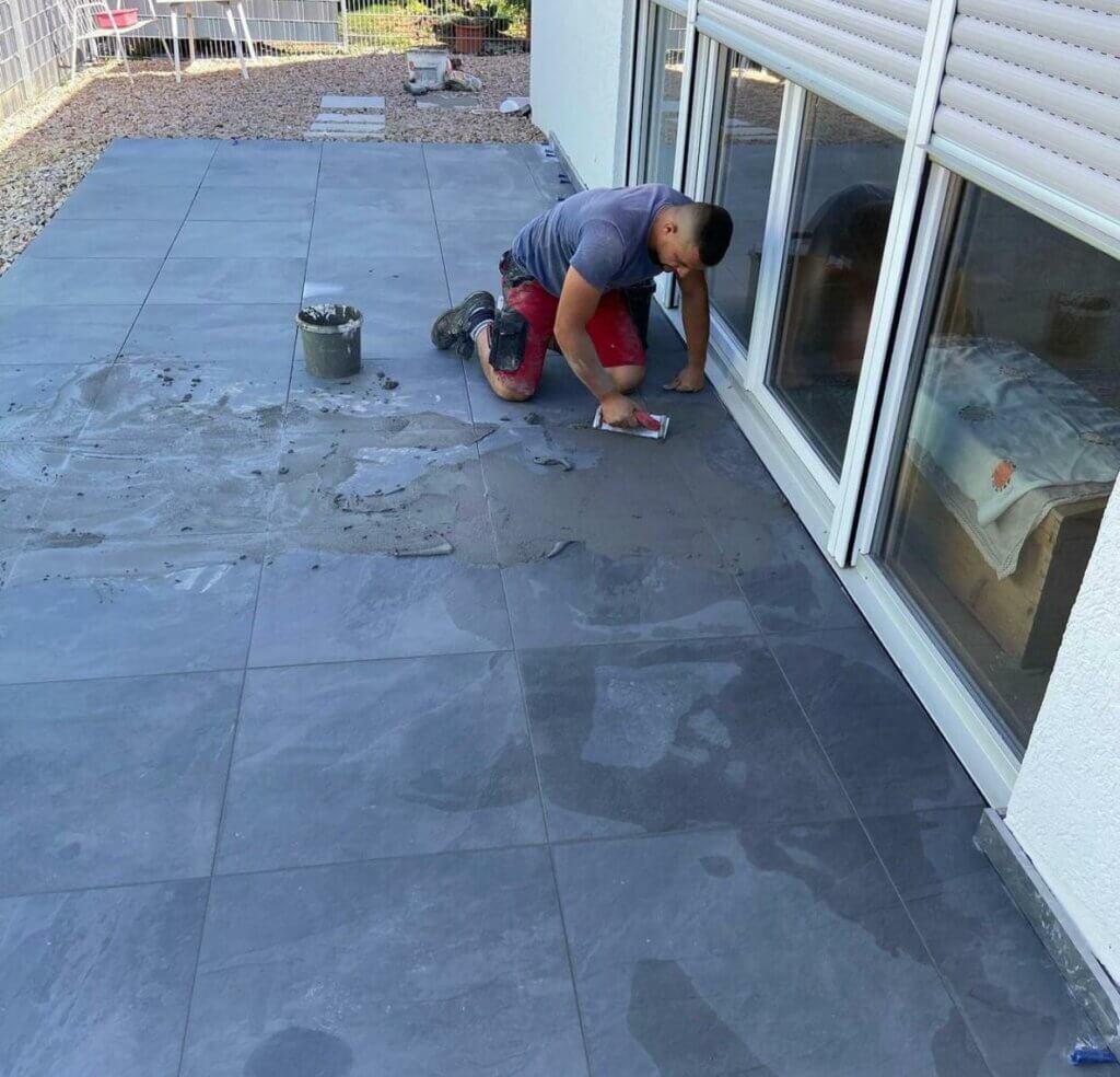 Person beim Terrassenplatten Verlegen